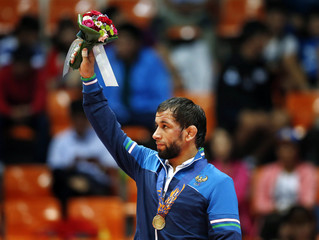 Uzbekistan's gold medal winner Kurbanov reacts during the victory ceremony of the Men's Freestyle 74 kg wrestling during the 2014 Asian Games in Incheon