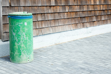 Old green dustbin, old striped wood as background