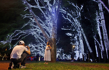 A man takes photos of his pregnant wife near trees decorated with Christmas lights at Ibirapuera Park in Sao Paulo