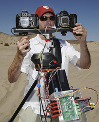 Matt Roman, an engineer with Space Science Systems, works with a photo system, in the desert near Baker, California