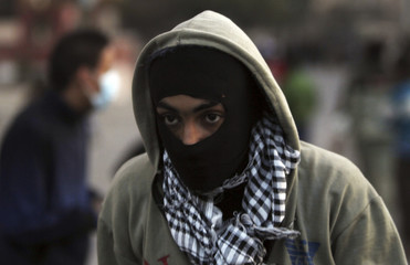 A member of the Black Bloc Egypt group flees from teargas released by riot police during clashes in Cairo