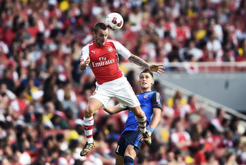 Arsenal's Mathieu Debuchy challenges Monaco's Lucas Ocampos during their Emirates Cup soccer match at the Emirates stadium in London
