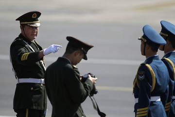 A commander gestures in front of the honour guard ahead of French President Francois Hollande and his companion Valerie Trierweiler's arrival in Beijing
