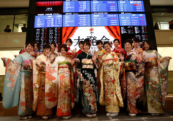 Women, dressed in ceremonial kimonos, pose for pictures in front of an electronic board showing stock prices after the New Year opening ceremony at the Tokyo Stock Exchange (TSE), held to wish for the success of Japan's stock market, in Tokyo