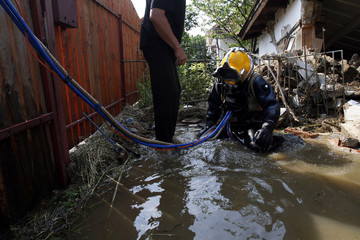 An industrial diver is seen after he turned off a water system tap at a flooded house in Felsozsolca
