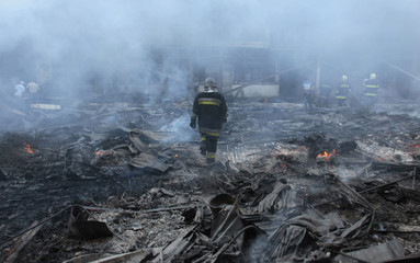 A firefighter walks at the scene of a fire which broke out at Comayaguela market in Tegucigalpa