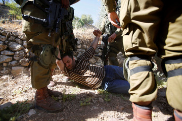 Israeli army soldiers detain a Palestinian as peace activists clean around Palestinian houses in Tal Rumaida in the West Bank city of Hebron