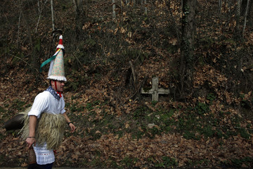 """A """"Joaldunak"""" carnival reveller parades past a cross on his way to Ituren during a traditional carnival celebration in the northern Spanish region of Navarra"""