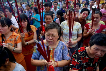 Myanmar Chinese women hold incenses sticks during a festival dedicated to Buddhist monk Shin Upagutta, celebrated by Myanmar's ethnic Chinese community, in Chinatown in Yangon