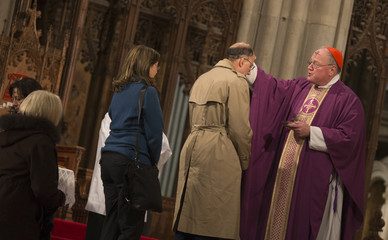 Cardinal Timothy Dolan delivers ashes to worshippers at Saint Patrick's Cathedral on Ash Wednesday in New York