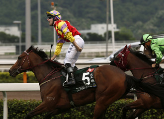 Berry riding Designs on Rome celebrates after crossing the finish line ahead of Moreira riding Military Attack during the Audemars Piguet QEII Cup at Shatin racetrack in Hong Kong