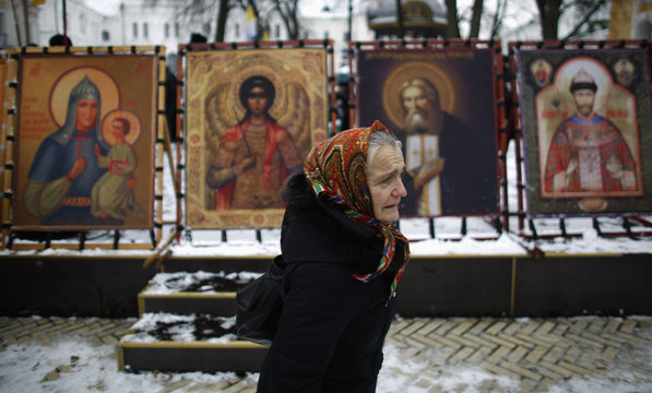 A believer walks in front of icons displayed in front of Kievo-Pecherskaya Lavra Cathedral, during a procession of relics and pictures of Eastern Orthodox saints commemorating the icon of St. Nicholas the Drenched, in Kiev