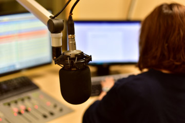 Rear view of female radio host working in front of a microphone on the radio station