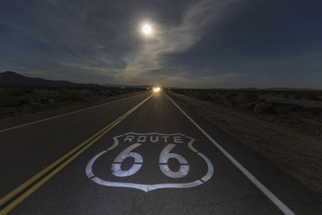 Fotobehang Route 66 Route 66 sign with full moon and oncoming headlights in the California Mojave desert.