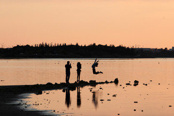 People take pictures during the sunset at a salt lake in Larnaca