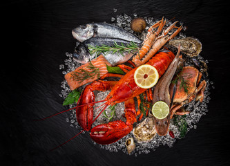 Wall Mural - Fresh tasty seafood served on black stone.