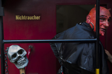 A man with devil make-up travels on HSB light railway through Harz mountains to celebrate Walpurgisnacht pagan festival