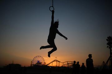 A man swings on rings on the Old Muscle Beach in Santa Monica