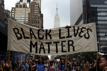 People take part in a protest against the killings of Alton Sterling and Philando Castile during a march through Manhattan