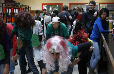 "Students look at demonstrators dressed as zombies dancing to the music of Michael Jackson's ""Thriller"" song during a protest at the cafeteria of the faculty of Political Science at Madrid's Complutense University"