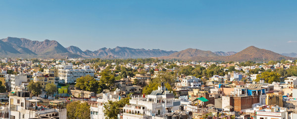 Panoramic view of buildings surrounded by green trees against blue sky in Udaipur, Rajastan, India. Mountains on background