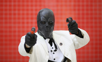 Brice Jones dressed as Black Mask from Batman poses for a photograph at the London supercomic convention at the Excel centre in east London