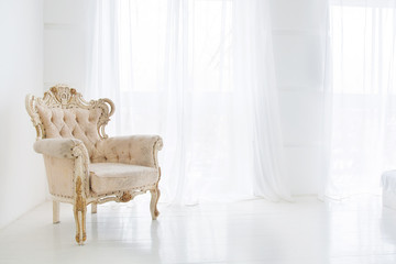 Vintage armchair against big windows with curtains in white interior