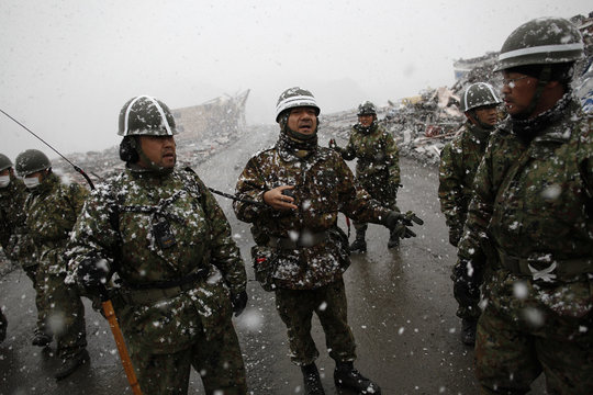 A Japan Self-Defense Force officer gives instruction to his team at the devastated residential area of the tsunami hit Otsuchi as heavy snow falls