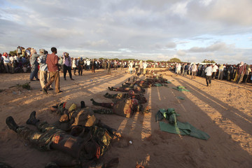 People stand near what al Shabaab rebels say are the bodies of 76 Burundian peacekeepers from the African Union Mission to Somalia killed during heavy fighting in Daynile district