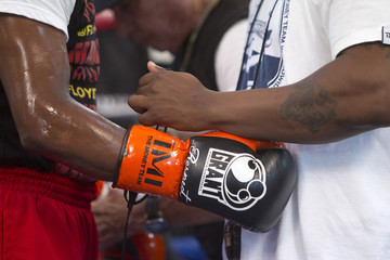 Undefeated boxer Floyd Mayweather Jr. of the U.S. gets help removing his gloves during a workout at the Mayweather Boxing Club in Las Vegas