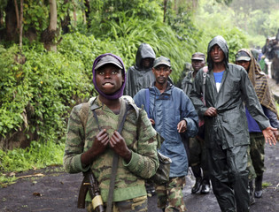 M23 rebel fighters walk as they withdraw near the town of Sake