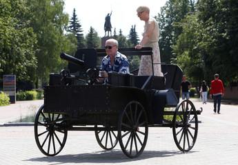 Couple poses for picture on top of replica of Russian Civil War Tachanka machine gun platform in Cheboksary