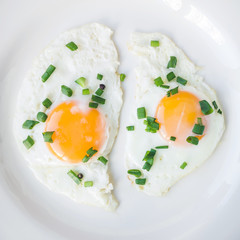 Fried eggs with green onion in white plate, close-up, top view