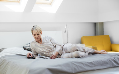 Pretty Caucasian woman lying in bed in the morning and enjoying reading a magazine.