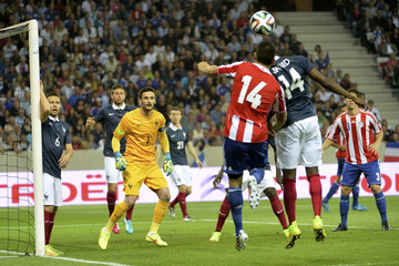 France's Blaise Matuidi challenges Paraguay's Junior Alonso as goalkeeper Hugo Lloris watches play during their international friendly soccer match at the Allianz Riviera soccer stadium in Nice