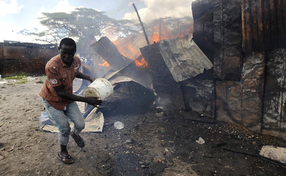 A trader runs away after attempting to extinguish fire with a bucket of water at the City Stadium open air market in Nairobi