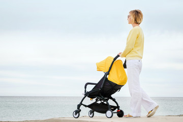 Young mother walking at the beach with baby stroller against cloudy sky