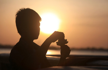 A boy is silhouetted as he prepares a lotus flower for sale in front of the Royal Palace in central Phnom Penh