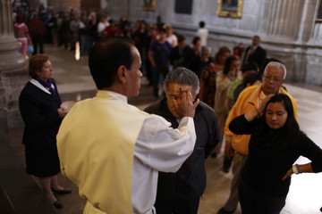 Catholic believer is sprinkled with ash during Ash Wednesday at the Metropolitan Cathedral in Mexico City