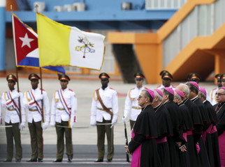 The Vatican flag is seen next to the Cuban flag during Pope Francis's arrival ceremony at the airport in Havana