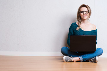 Young creative woman sitting in the floor with laptop. Casual blogger woman.