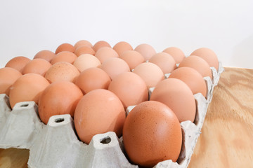 A pack of eggs on wooden background.