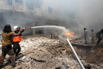 Civil defence members try to put out a fire at a market hit by air strikes in Idlib city
