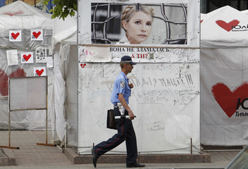 A police officer walks past tents at a protest camp set up by supporters of Tymoshenko in central Kiev