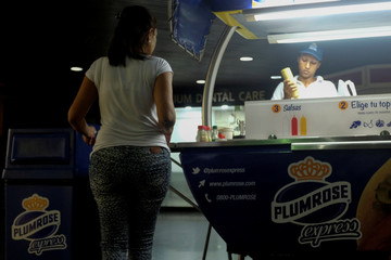 A vendor prepares a hot dog for a customer at a Plumrose stand in Caracas