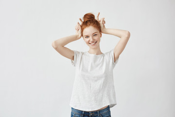 Beautiful redhead girl smiling showing hare hands.