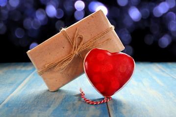 красное сердце и подарок  на синих деревянных досках на фоне блесток