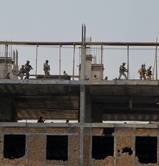 Security forces are seen on the rooftop after it was recaptured from Taliban insurgents who took over a building in Kabul