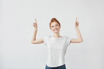 Cute ginger girl with freckles smiling pointing fingers up.