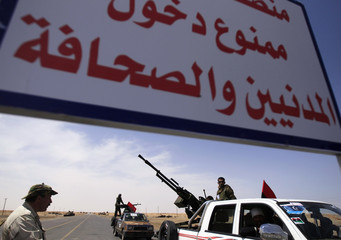 Rebel fighters stand guard with their weapons and vehicles at the frontline, along the western entrance of Ajdabiya